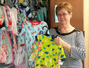 Carolyn Mills holding up a new pair of children's pajamas. In the background there are many more pajamas of different colors hanging in a closet